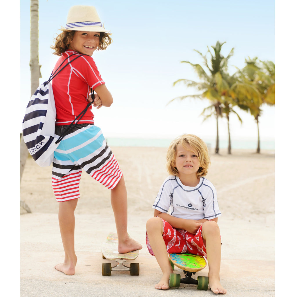 2 boys on beach. One wearing classic surfer style long swim shorts in blue, red, charcoal and white stripe