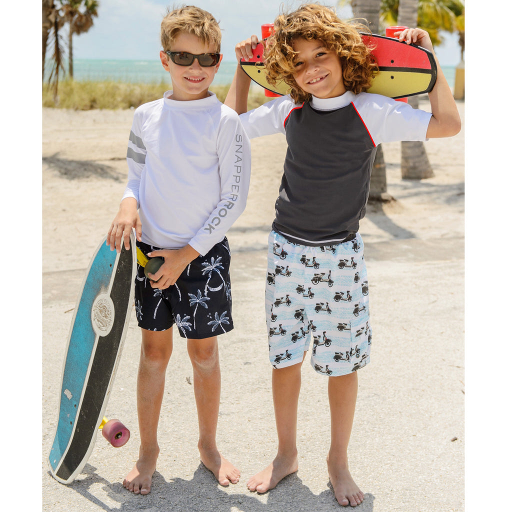 2 boys on beach. 1 boy wearing retro vespa print long swim shorts in pale blue and white with black waistband. Worn with grey/white short sleeve rash vest