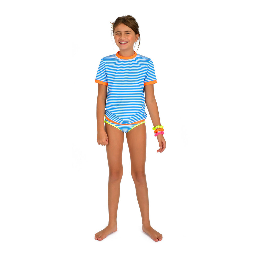Front view of girl wearing vivid blue stripe rash vest. Short sleeve with contrast bright orange trim