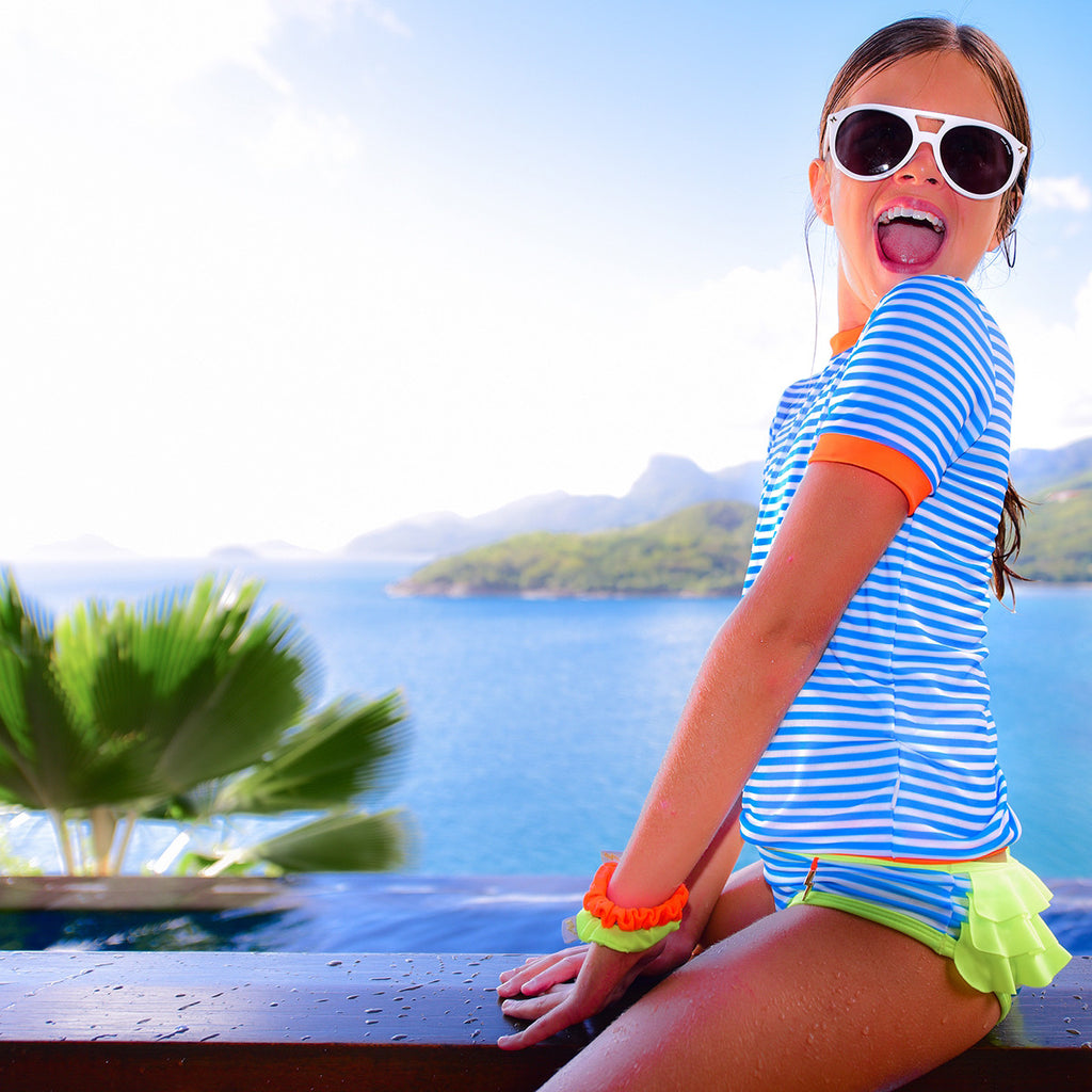 Girl by beach wearing vivid blue stripe rash vest. Short sleeve with contrast bright orange trim.