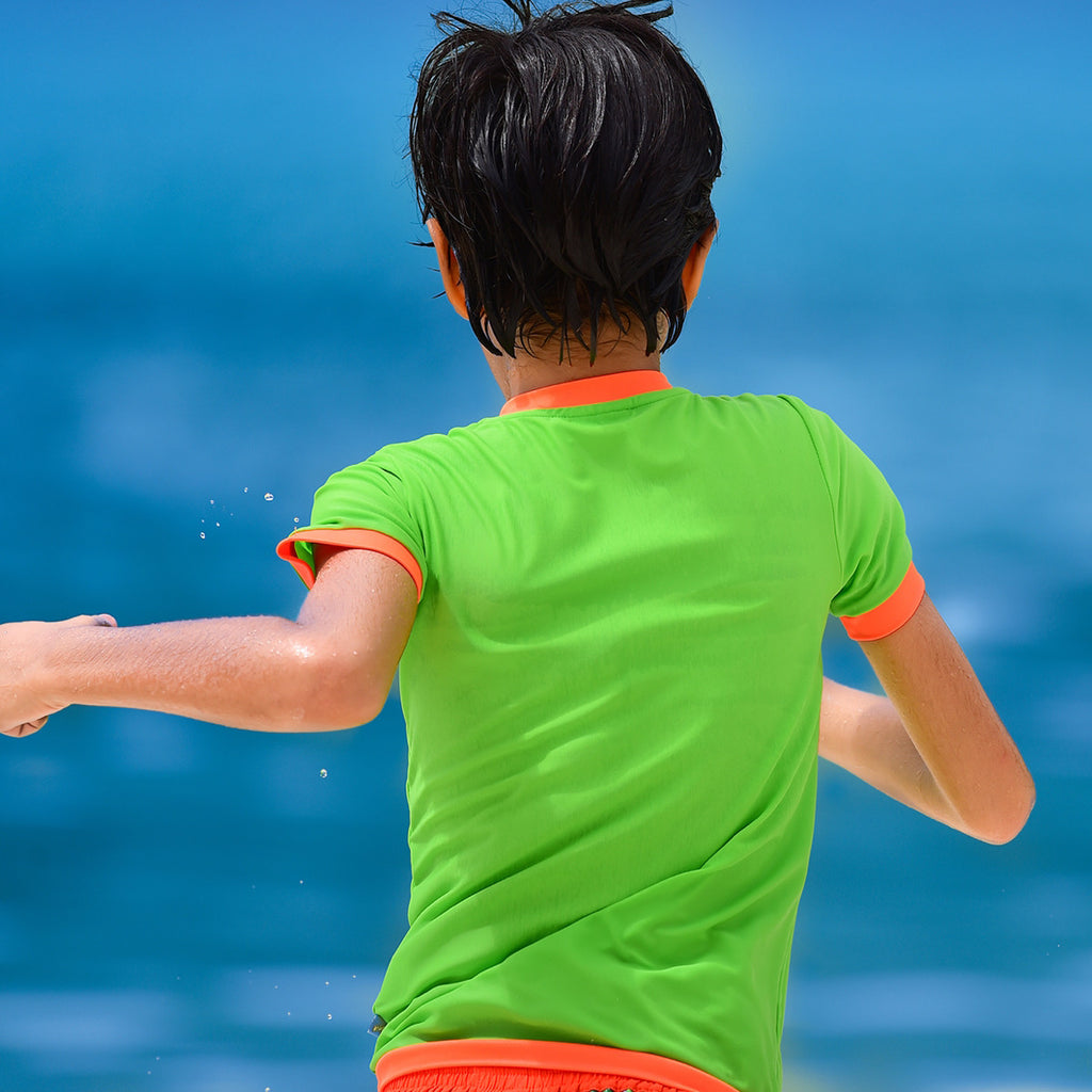 Boy running into sea wearing neon green rash vest. Short sleeve with contrast orange trim
