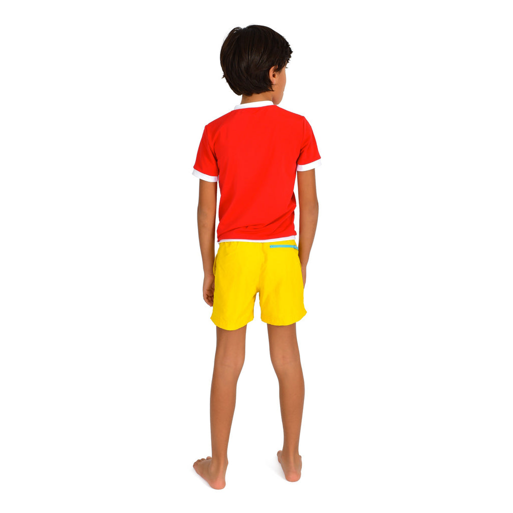 Back view of boy wearing bright red rash vest. Short sleeve with contrast white trim