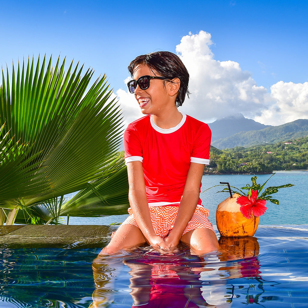 Boy sitting on pool edge wearing bright red rash vest. Short sleeve with contrast white trim