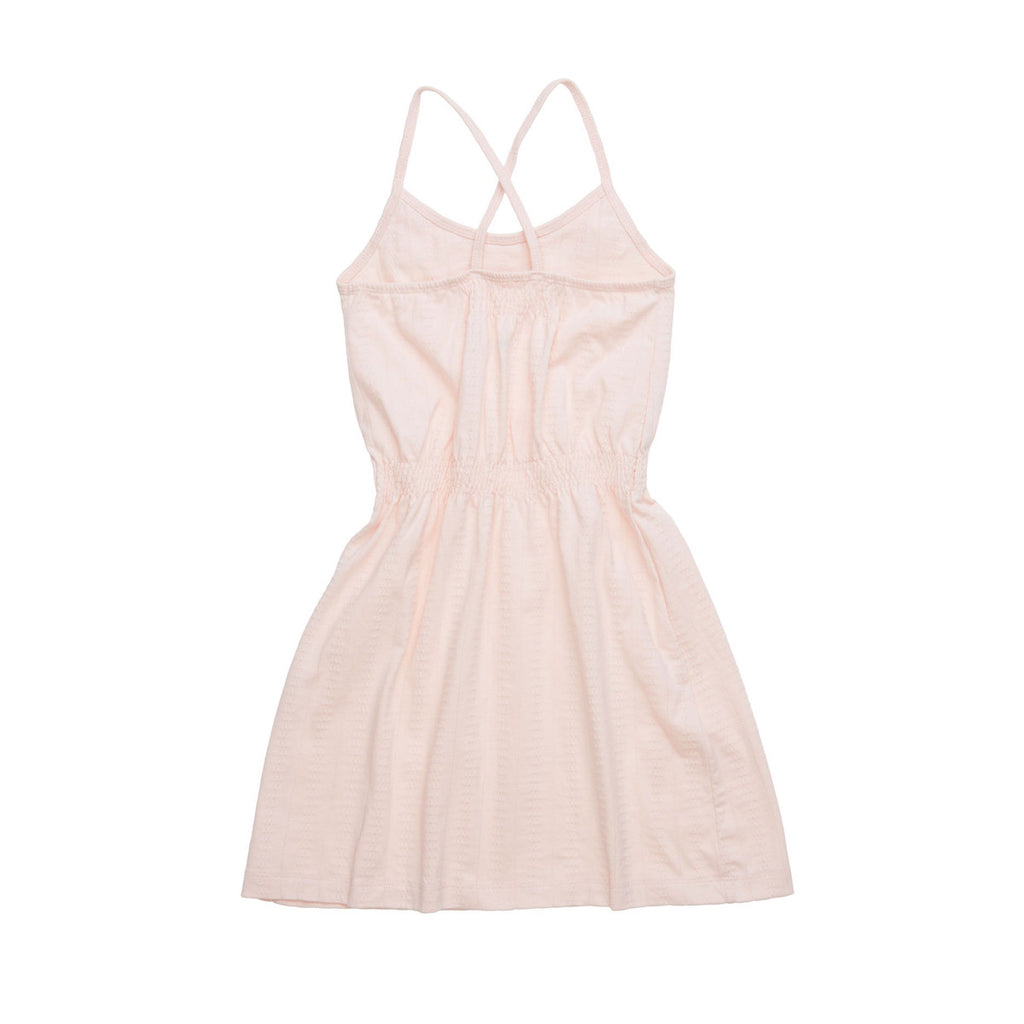 Back view of pretty pale pink beach dress with tucked waist, crossover back straps and ruffle detail to neckline