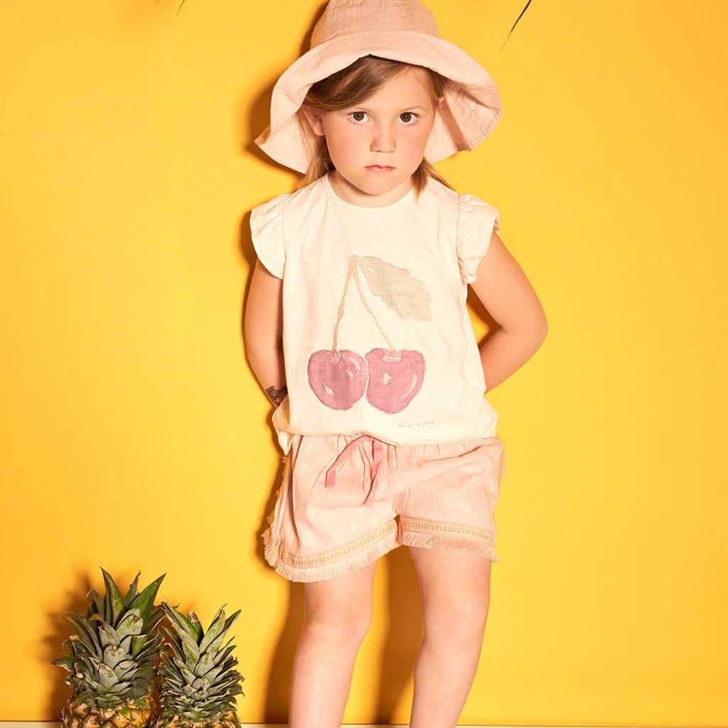 Girl wearing pale rose cap sleeve t-shirt with large cherry print to front. Soft cotton mix with button fastening to reverse. Paired with Hella pale pink shorts