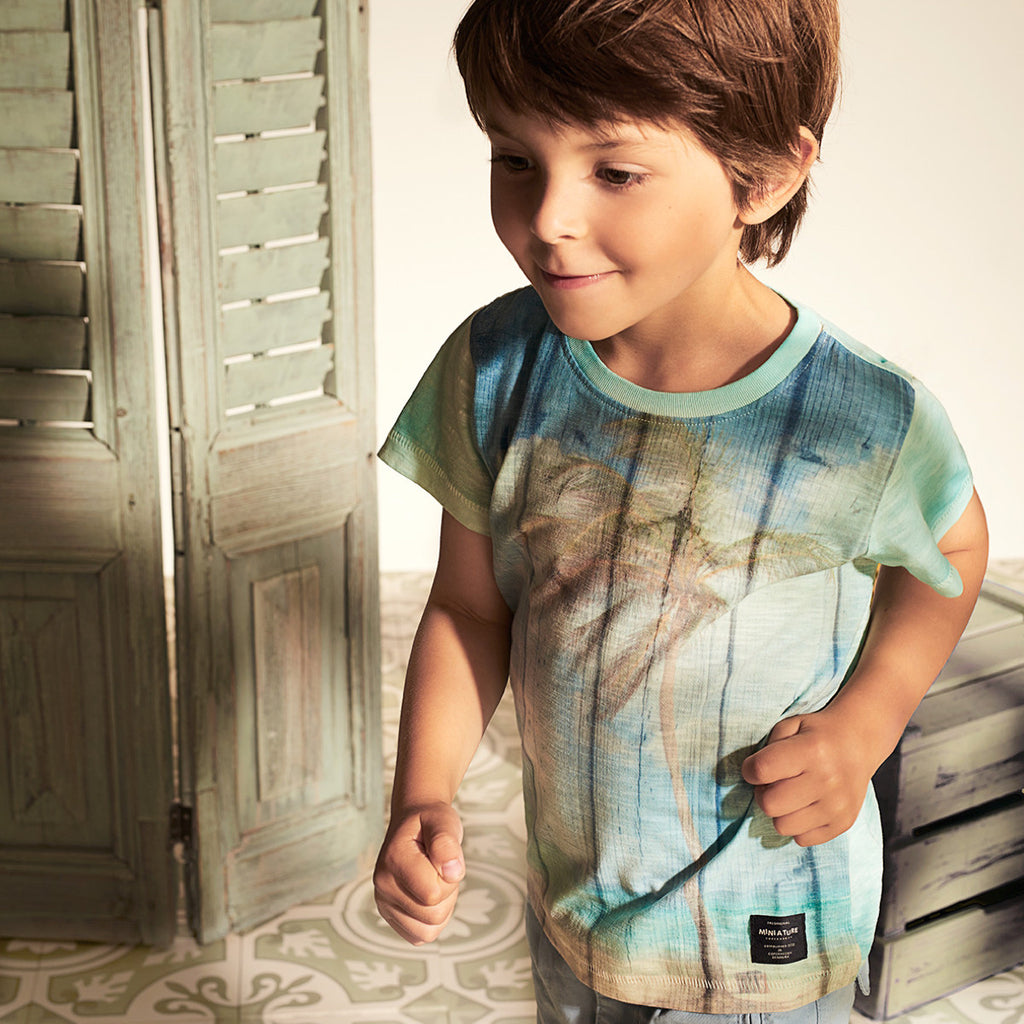 Boy wearing pale blue t-shirt with retro beach and palm print. Washed-look finish in soft cotton mix