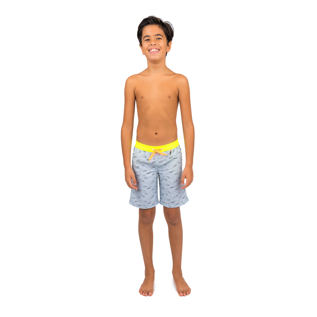 Front view of boy wearing grey tailored swim shorts with fun flying paper planes print. Adjustable waist with contrast neon yellow waistband