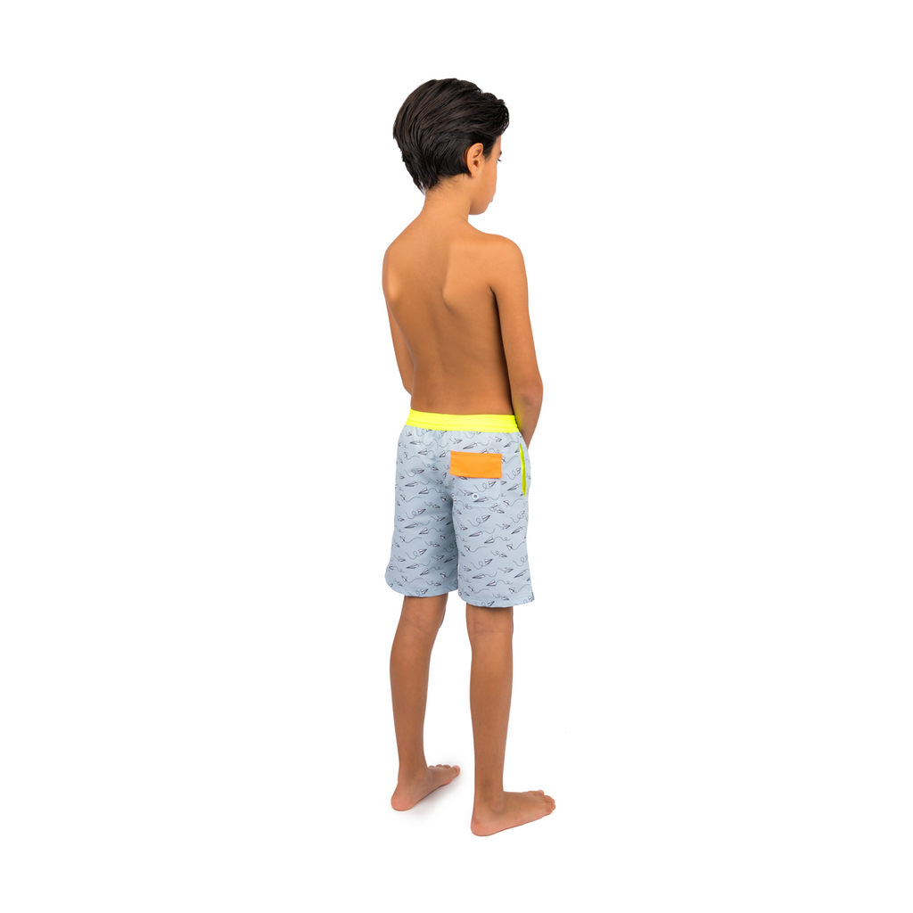 Back view of boy wearing grey tailored swim shorts with fun flying paper planes print. Adjustable waist with contrast neon yellow waistband
