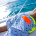 Boy lying on boat in sea wearing grey tailored swim shorts with fun flying paper planes print. Adjustable waist with contrast neon yellow waistband