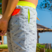 Boy standing on the beach wearing grey tailored swim shorts with fun flying paper planes print. Adjustable waist with contrast neon yellow waistband