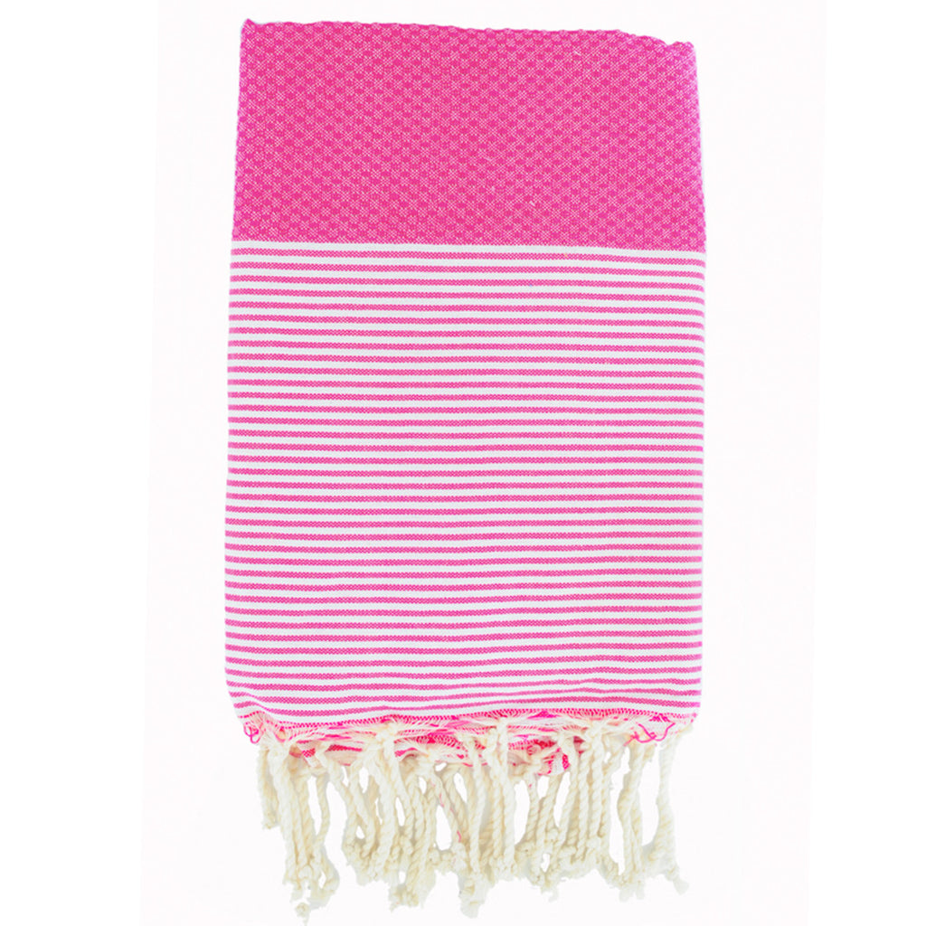Folded cotton hammam towel with honeycomb weave in vibrant pink colour with pink/white stripe detail and tassel ends