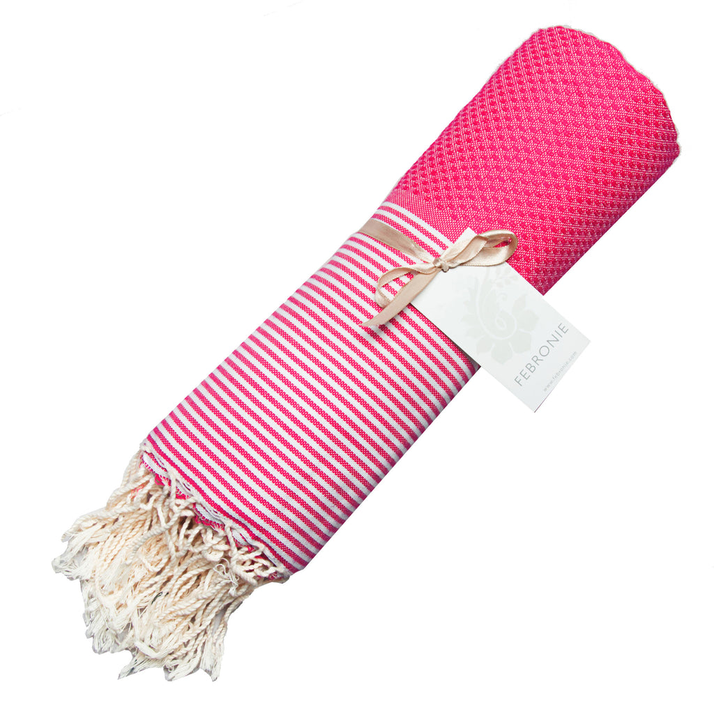 Rolled cotton hammam towel with honeycomb weave in vibrant pink colour with pink/white stripe detail and tassel ends
