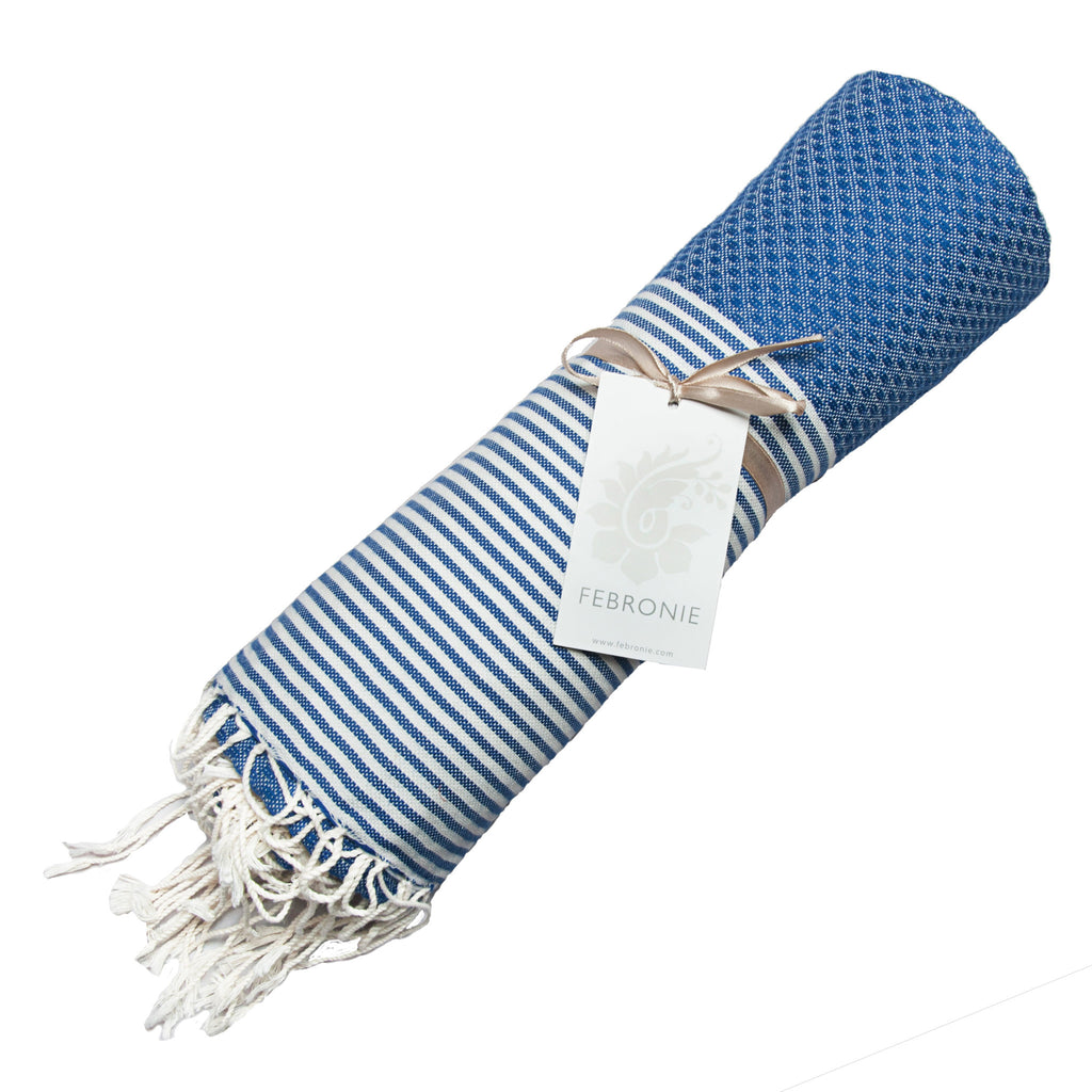 Rolled cotton hammam towel with honeycomb weave in striking mid-blue colour with blue/white stripe detail and tassel ends