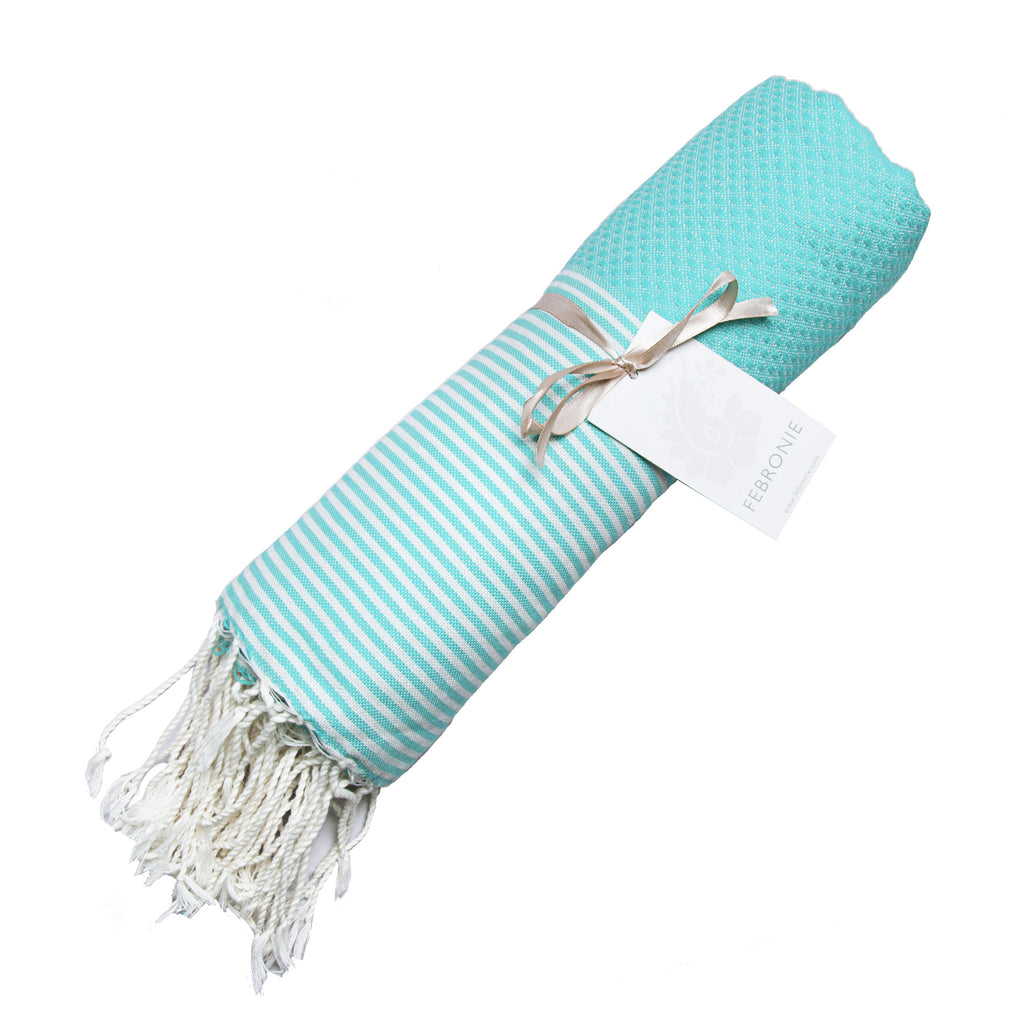 Rolled cotton hammam towel with honeycomb weave in bold aqua colour with aqua/white stripe detail and tassel ends