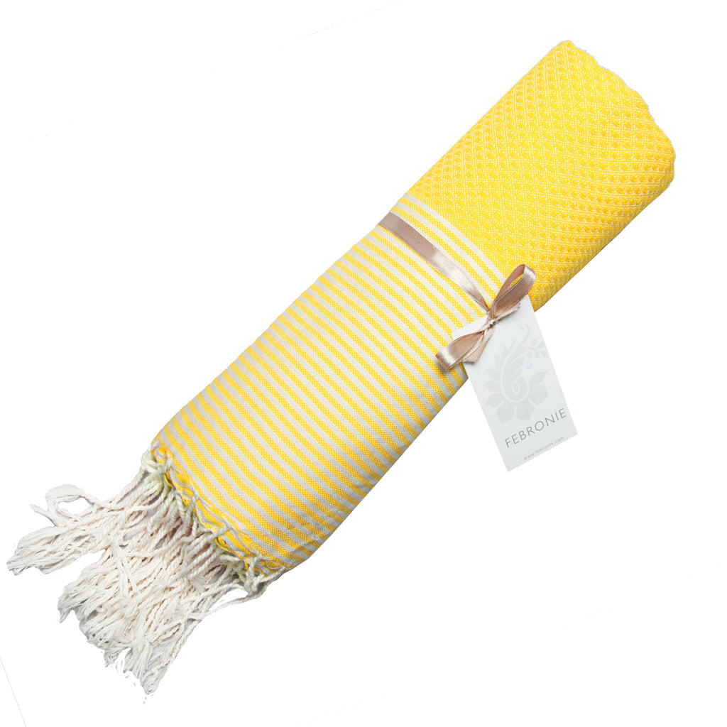 Rolled cotton hammam towel with honeycomb weave in striking yellow colour with yellow/white stripe detail and tassel ends
