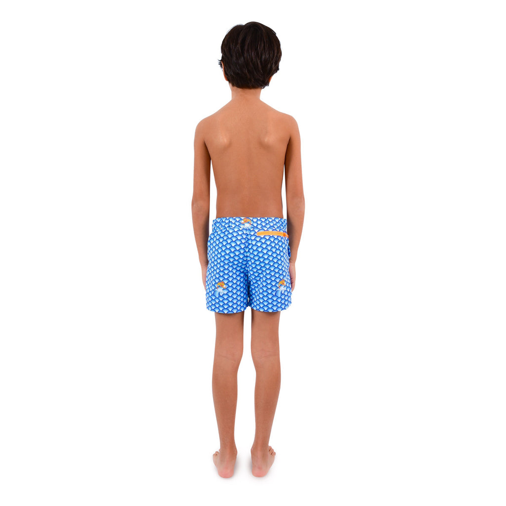 Back view of boy wearing vibrant blue wave pattern tailored swim shorts. Adjustable waist, contrast zip, side pockets, quick drying fabric