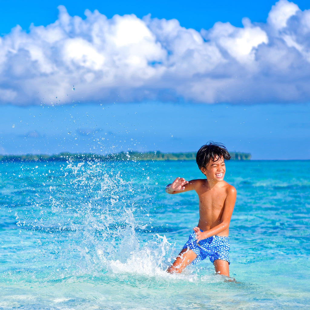 Boy running in sea wearing vibrant blue wave pattern tailored swim shorts. Adjustable waist, contrast zip, side pockets, quick drying fabric