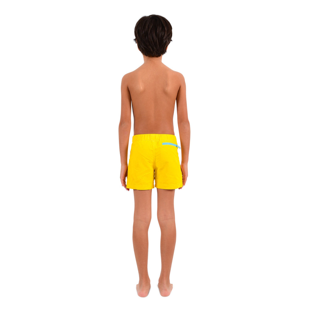 Back view of boy wearing bright yellow tailored swim shorts with contrast zip detail. Adjustable waist, side pockets, quick drying fabric