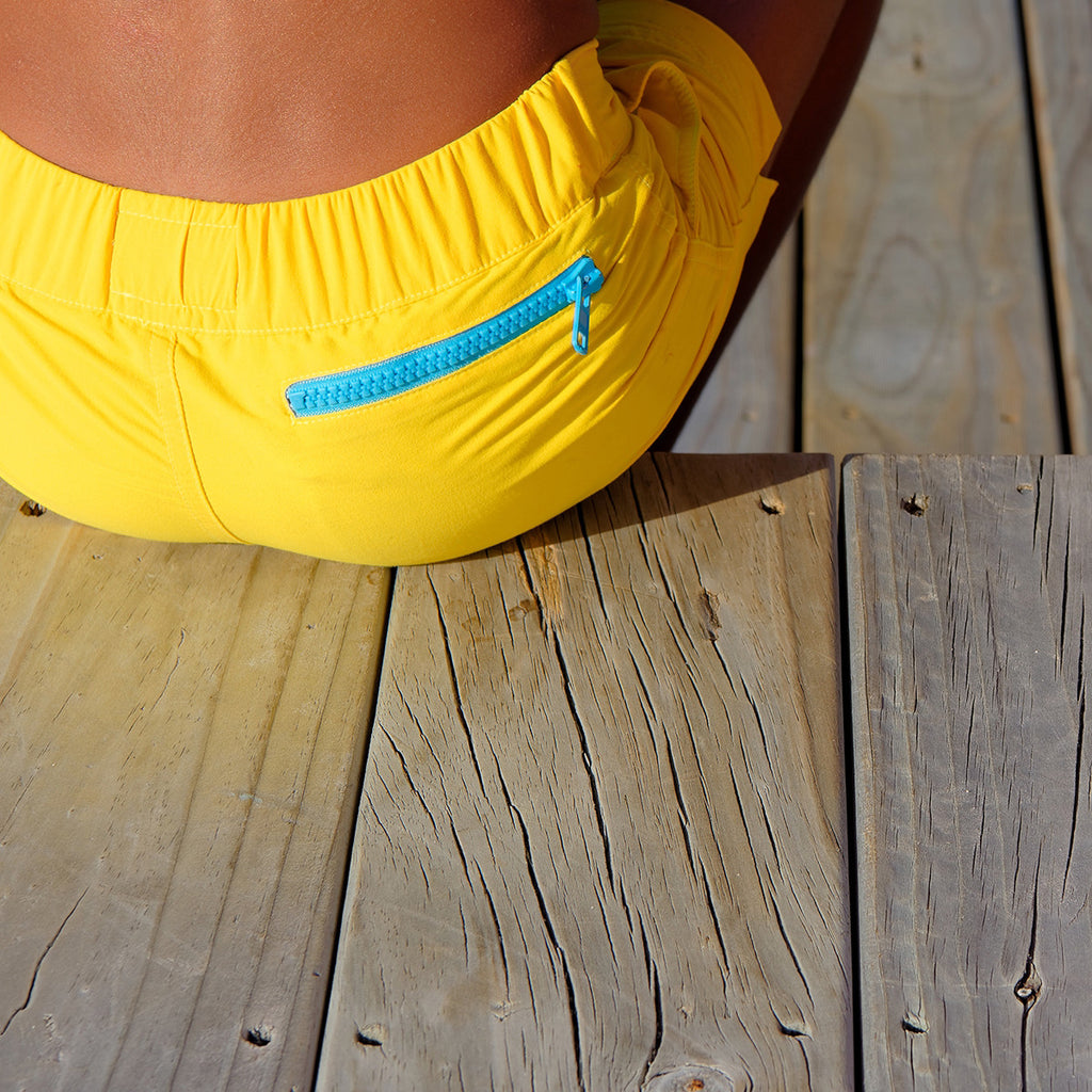 Close up view of back of bright yellow tailored swim shorts with contrast zip detail. Adjustable waist, side pockets, quick drying fabric