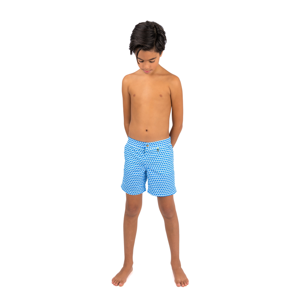 Front view of boy wearing blue geometric cube pattern boys swim shorts.