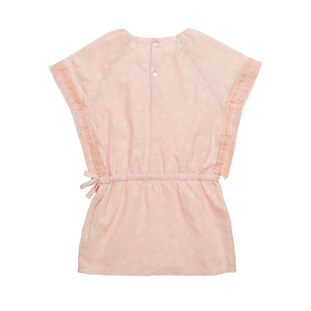 Back view of pretty light pink short dress with subtle bubble allover print. Drawstring dropped waist with tie side. Wide sleeve opening with embroidered detail