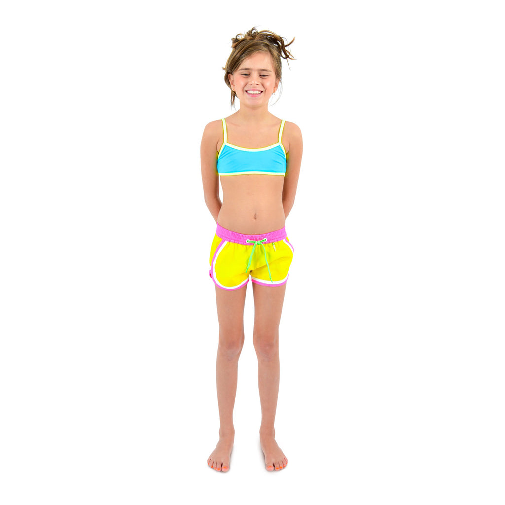 Front view of girl wearing funky boxer-style elasticated shorts with pockets. Vibrant sunshine yellow with contrast bright pink waistband, trim and tie