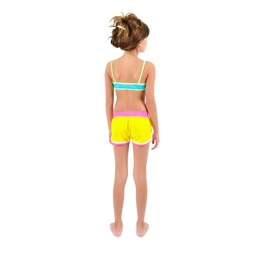 Back view of girl wearing funky boxer-style elasticated shorts with pockets. Vibrant sunshine yellow with contrast bright pink waistband, trim and tie