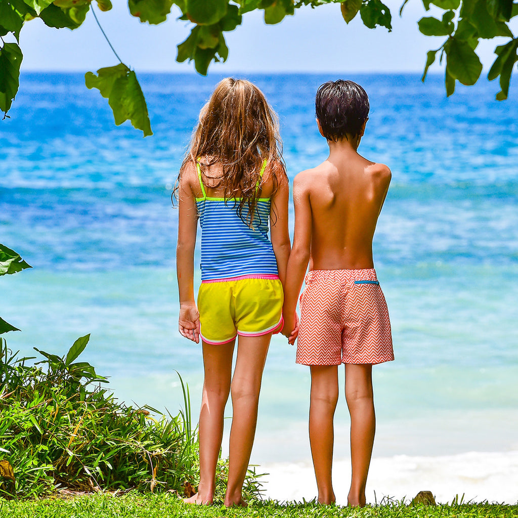 Back view of girl and boy by beach with girl wearing funky boxer-style elasticated shorts with pockets. Vibrant sunshine yellow with contrast bright pink waistband, trim and tie