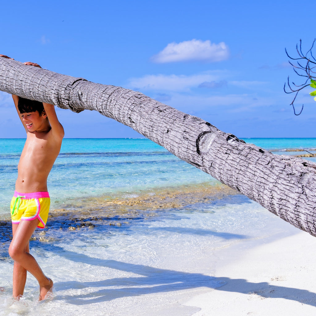 Boy on beach wearing funky boxer-style elasticated shorts with pockets. Vibrant sunshine yellow with contrast bright pink waistband, trim and tie