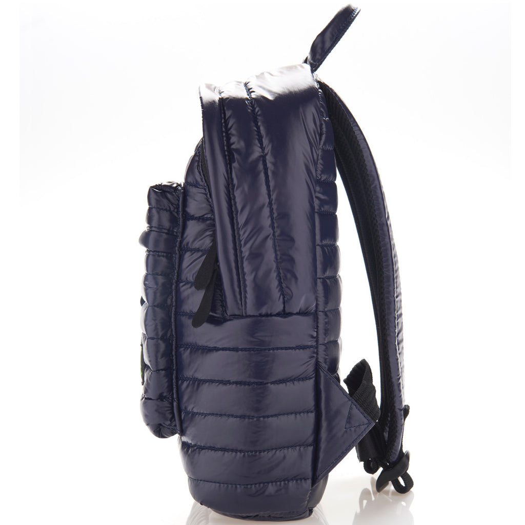 Side view of navy blue small backpack. Made from durable shiny nylon puffer material with quality components. Large main section and small front pocket