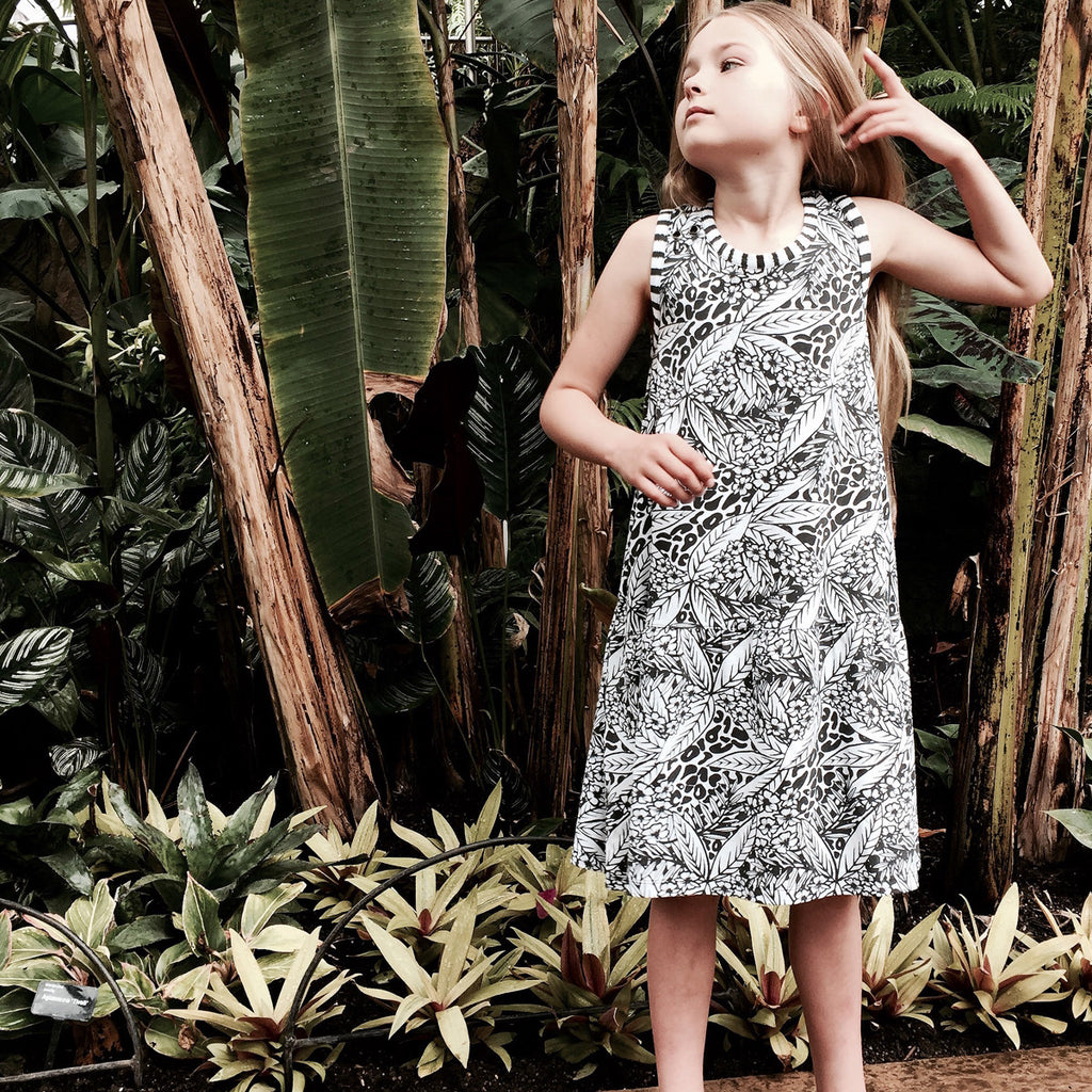 Girl wearing cotton beach dress in striking and bold black and white painted tropical and animal print