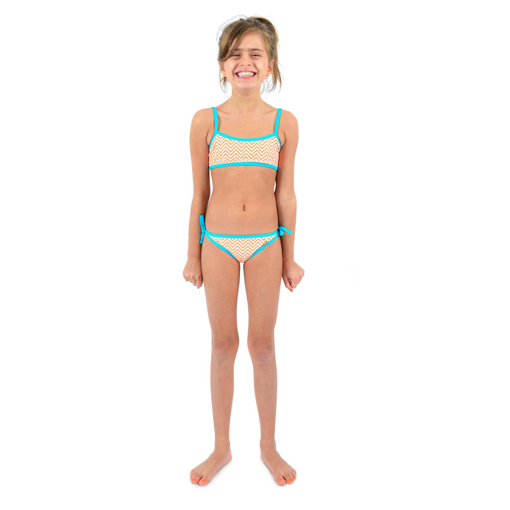 Front view of girl wearing bright orange chevron bikini with contrast turquoise trim. Classic tie side bottoms with simple scooped bikini top