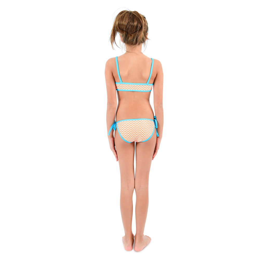 Back view of girl wearing bright orange chevron bikini with contrast turquoise trim. Classic tie side bottoms with simple scooped bikini top