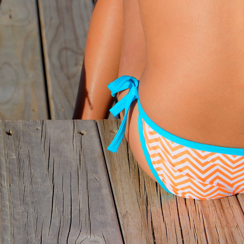 Close up of girl by beach wearing bright orange chevron bikini with contrast turquoise trim. Zoom is on back of bikini bottoms with tie side