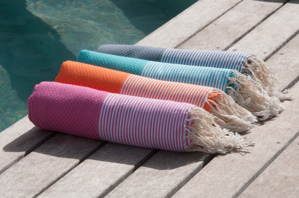 Row of 4 bright coloured rolled foutas on poolside deck