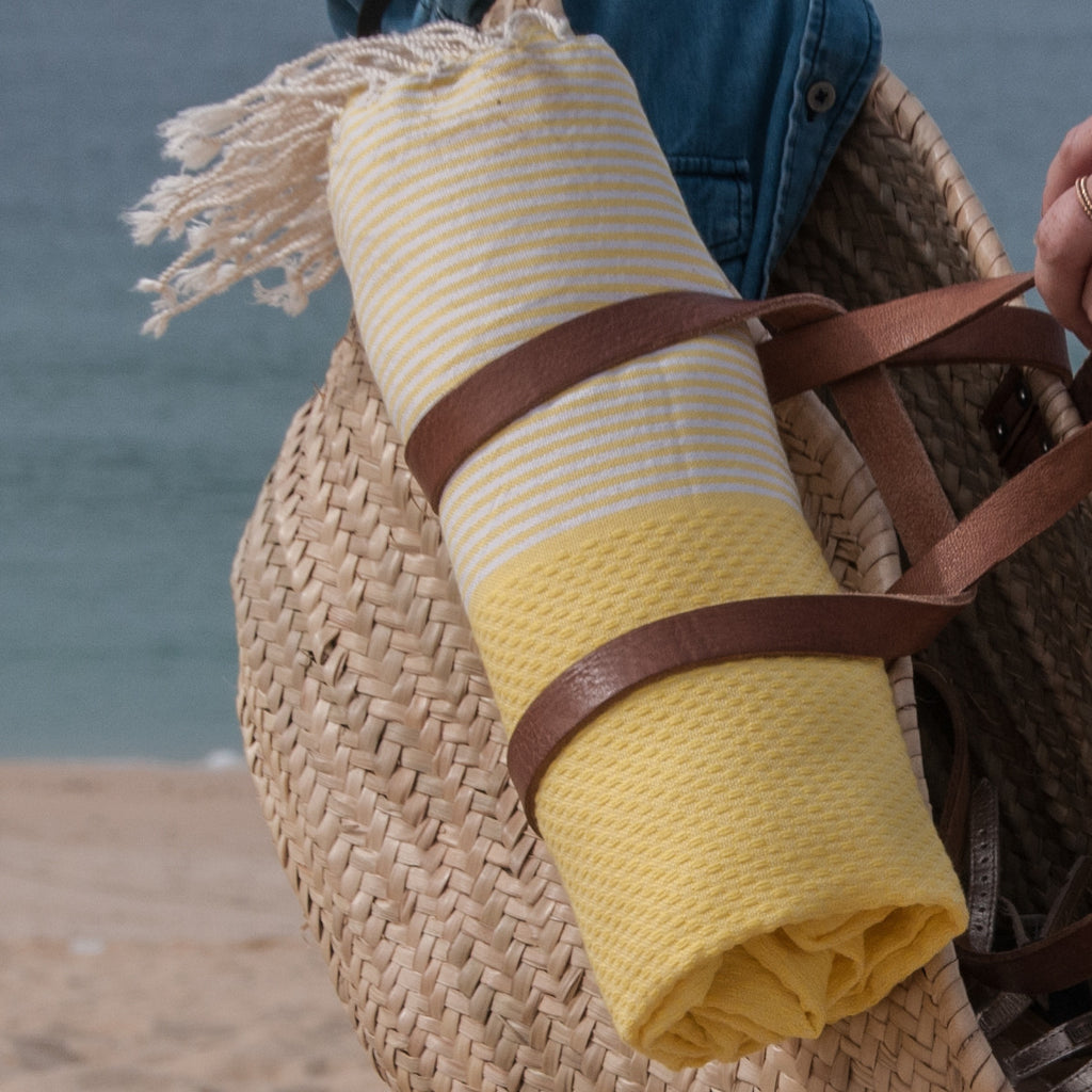 Rolled up yellow fouta attached to beach bag