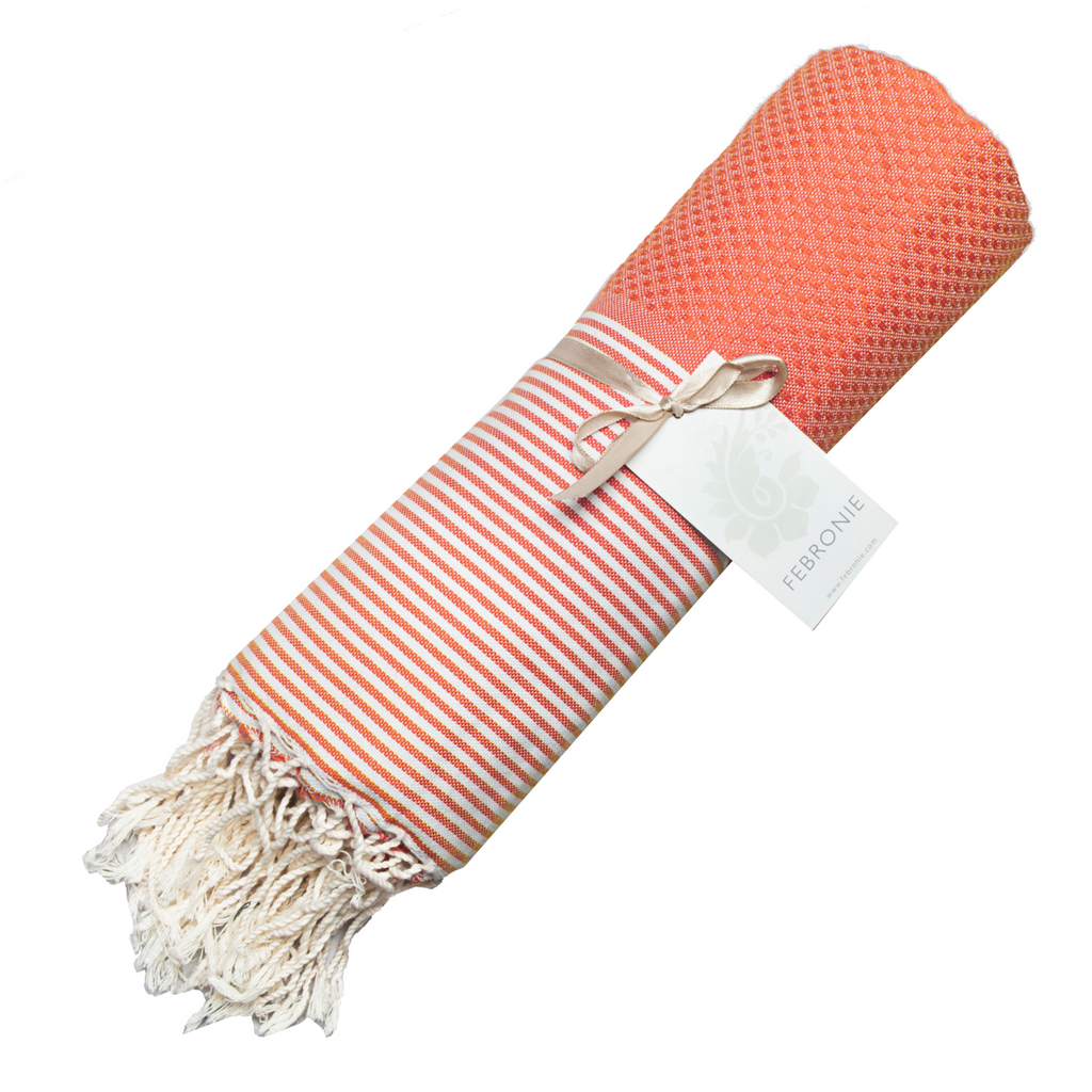 Rolled cotton hammam towel with honeycomb weave in coral orange colour with coral/white stripe detail and tassel ends