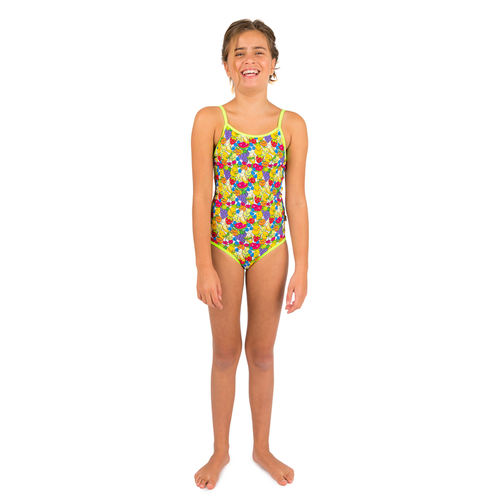 Front view of girl wearing tutti frutti print swimsuit. Multi colour fruit mix with contrast neon green trim and straps