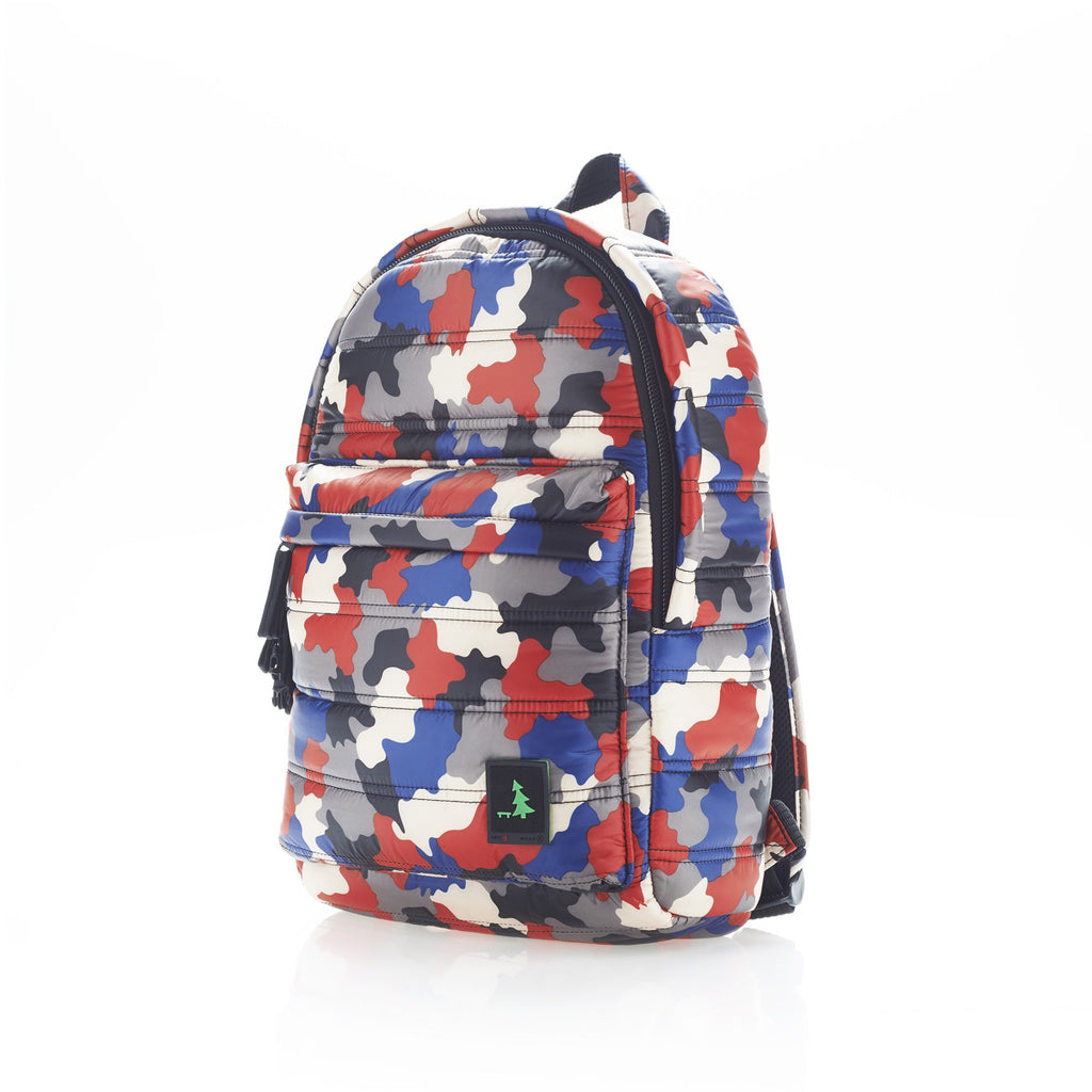 Angle side view of red/blue camo mid-size backpack. Made from durable nylon puffer material with quality components and a unique fastening system. Large main section and small front pocket