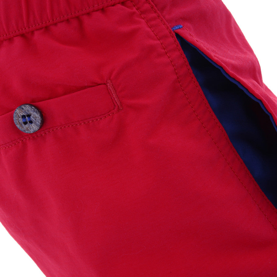 Side view of boys red tailored swim shorts showing pocket detail with contrast blue lining