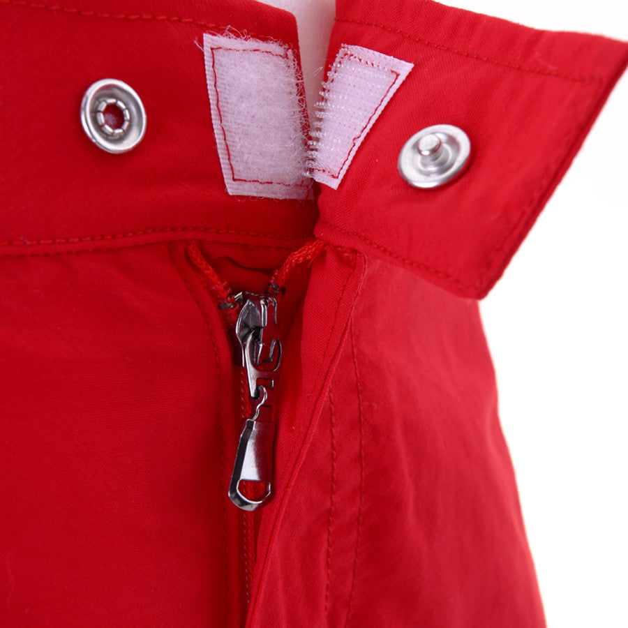 Front detail view of boys red tailored swim shorts showing velcro and popper fastening