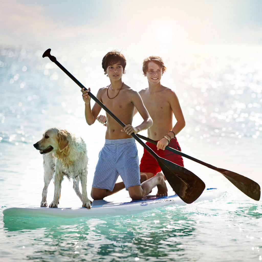 Boys on surf board wearing red tailored swim shorts and blue and white stripe tailored swim shorts