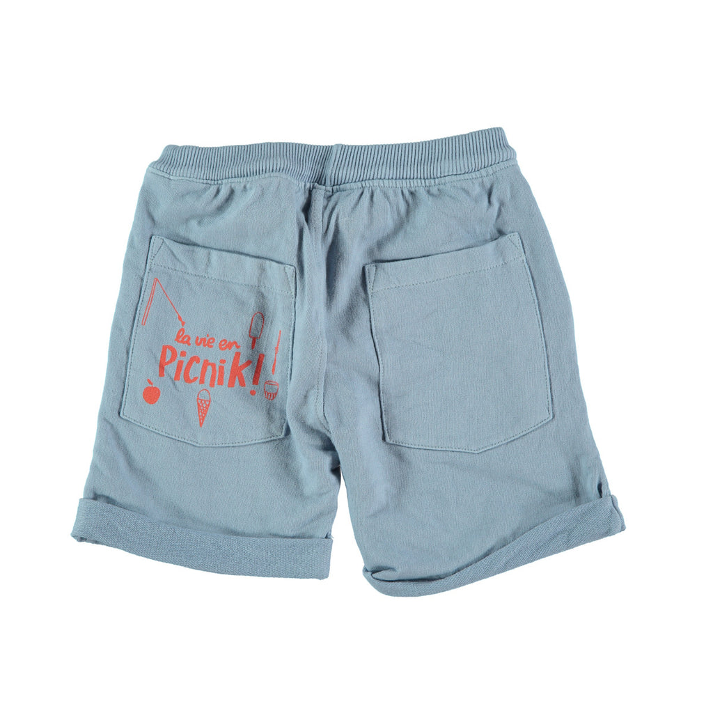 Back view of jogger style cotton shorts in mid blue with 'picnik' design on back pocket. 100% cotton with loose turn up, elasticated waist and tie string to front. Pockets at side and back