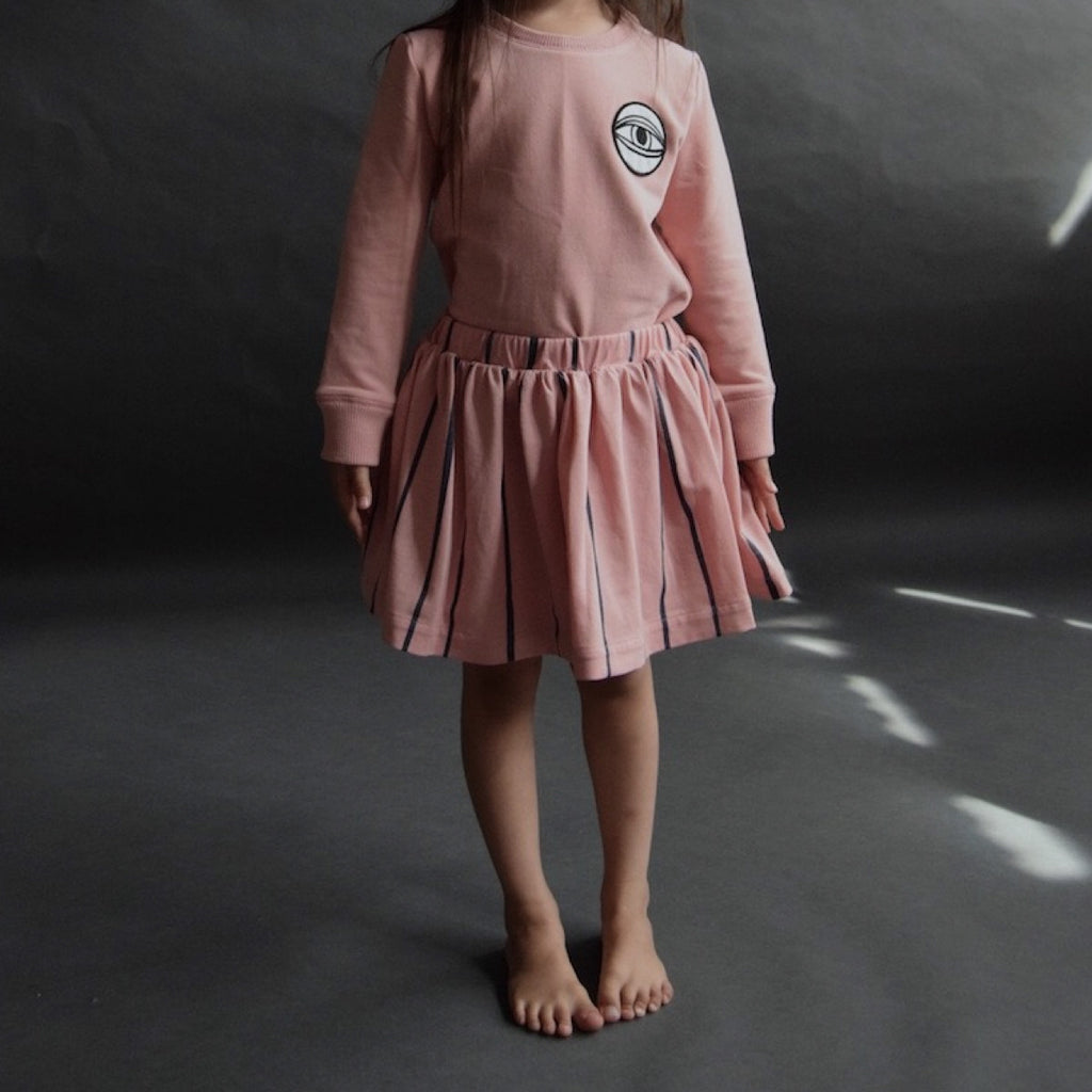 Girl wearing soft pink full short cotton skirt with wide blue stripe detail. Elasticated waist. Paired with pink jumper