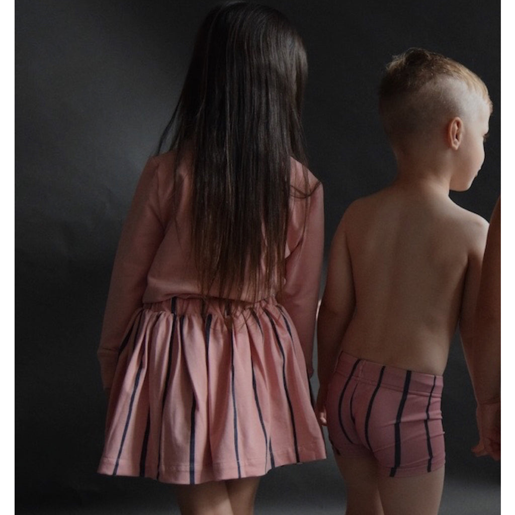 Back view of girl wearing soft pink full short cotton skirt with wide blue stripe detail. Elasticated waist. Pictured with boy wearing swim trunks