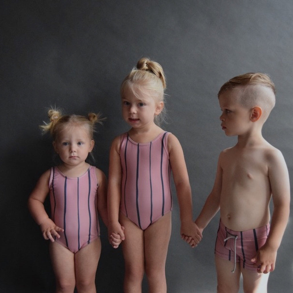 2 girls wearing soft pink classic shaped swimsuit with wide blue stripe detail. Pictured with boy wearing pink swim trunks