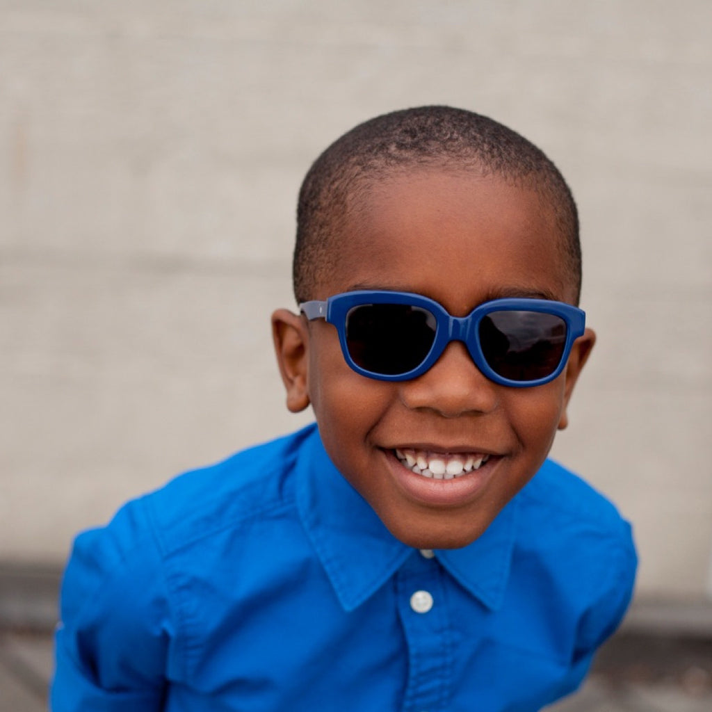 Boy wearing solid navy acetate frame sunglasses with grey polarised lens