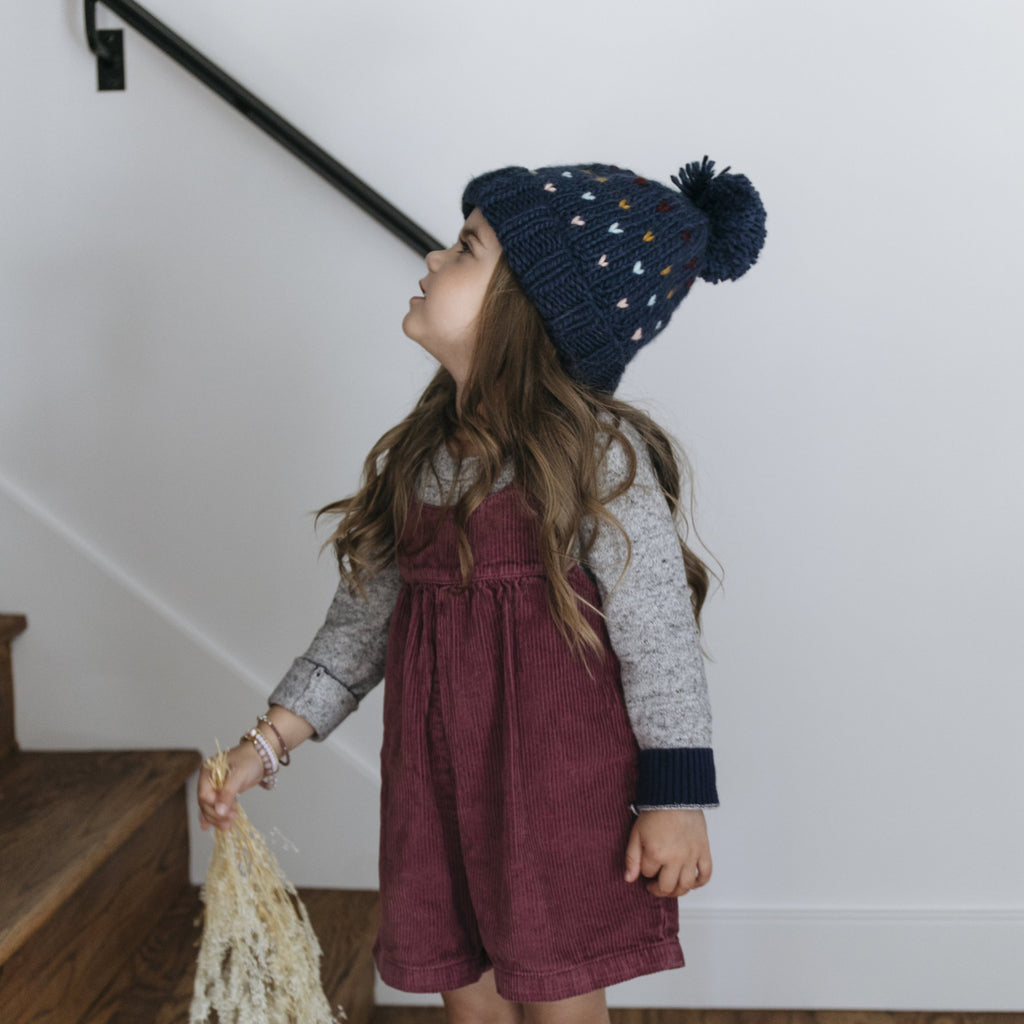 Navy blue beanie with multi color fair isle hearts in rainbow pattern