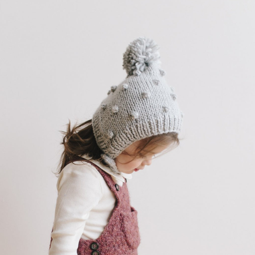 Grey bonnet with popcorn knit, pom, and wooden button