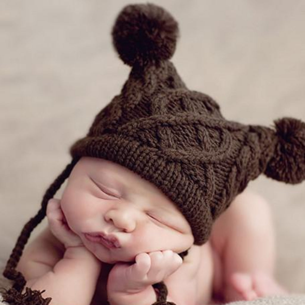 Brown cable knit beanie with tassels and double poms
